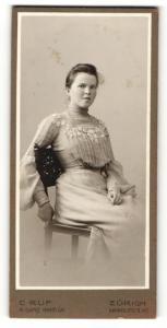 Fotografie C. Ruf, Zürich, Portrait sitzende junge Dame in hübscher Kleidung