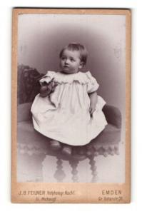 Fotografie J. B. Feilner, Emden, Kleinkind in weissem Kleidchen sitzt auf Sessel