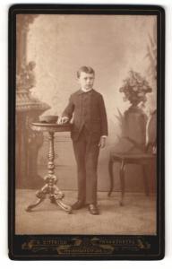 Fotografie R. Dittrich, Frankenberg, Portrait niedlicher Bube im Anzug am Tisch stehend