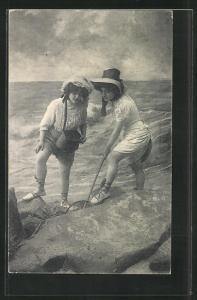 AK Bademode, zwei junge Damen mit kurzen Röcken und Hüten buddeln am Strand