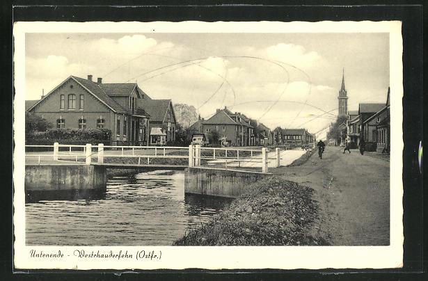 AK Westrhauderfehn / Ostfr., Untenende, Blick auf Ufer mit Brücke, Kirchturm und Häuser 0