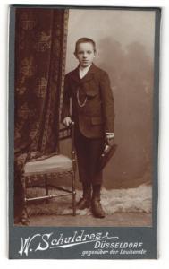 Fotografie W. Schuldres, Düsseldorf, Portrait niedlicher Bube mit Schirmmütze im Anzug