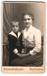 Fotografie Ferdinand Stracke, Reichenberg, Portrait lächelnde Mutter mit niedlichem Buben im Matrosenanzug