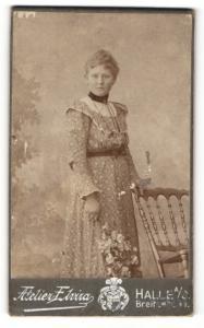 Fotografie Atelier Elvira, Halle a. S., Portrait hübsch gekleidete Dame mit Blumen an Stuhl gelehnt