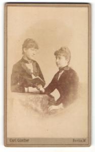 Fotografie Carl Günther, Berlin-W, Portrait zwei junge Damen in eleganter Kleidung mit Buch