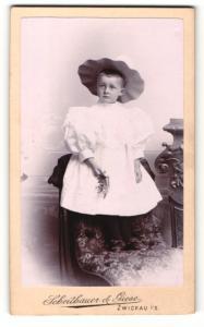 Fotografie Scheithauer & Giese, Zwickau i / S., Portrait kleines Mädchen im weissen Kleid mit Hut auf Sessel stehend