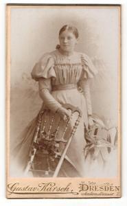 Fotografie Gustav Karsch, Dresden, Portrait hübsch gekleidete Dame mit Blume an Stuhl gelehnt