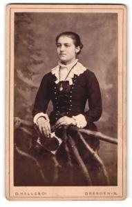 Fotografie O. Halle & Co., Dresden, Portrait hübsch gekleidete Dame mit Buch an Zaun gelehnt