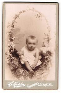 Fotografie H. Michler, Grottau, Portrait niedliches Kleinkind im weissen Hemd im Korbstuhl sitzend