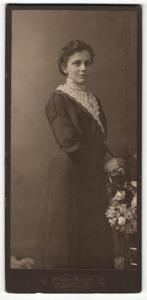 Fotografie Atelier Apollo, Dresden-N, Portrait hübsch gekleidete Dame mit Blumen an Stuhl gelehnt