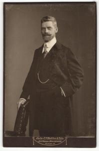 Fotografie C. F. Beddies & Sohn, Braunschweig, Portrait elegant gekleideter Herr mit Bart an Stuhl gelehnt