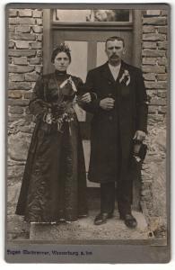 Fotografie Eugen Glasbrenner, Wasserburg / Inn, Portrait elegant gekleidetes Paar mit Blumenstrauss und Ansteckblume