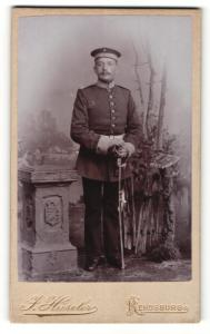 Fotografie J. Hüscher, Rendsburg, Portrait charmant blickender Soldat in interessanter Uniform