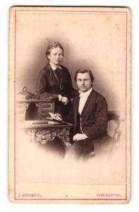 Fotografie J. Kosmehl, Magdeburg, Portrait elegant gekleidetes Paar am Tisch sitzend