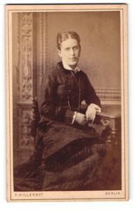Fotografie F. Hiller & Co., Berlin, Portrait elegant gekleidete Dame am Tisch sitzend