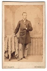 Fotografie P. S. Cramer, Nürnberg, Portrait elegant gekleideter Herr mit Buch an Tisch gelehnt