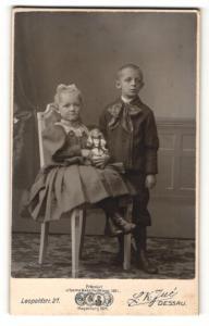 Fotografie L. K. Jue, Dessau, Portrait bezauberndes Kinderpaar in hübscher Kleidung und Puppe