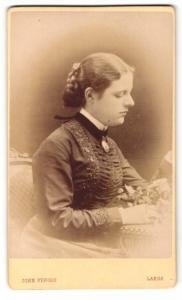Fotografie John Fergus, Largs, am Tisch sitzende Frau mit Dutt im schwarzen Kleid