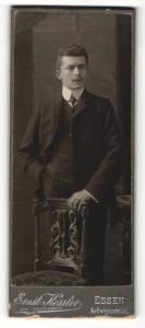 Fotografie Ernst Kessler, Essen, Portrait elegant gekleideter Herr mit Schnurrbart an Stuhl gelehnt