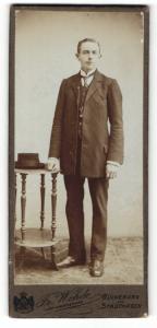 Fotografie Dr. Wehde, Bückeburg, Portrait elegant gekleideter Herr mit Hut an Tisch gelehnt