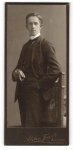 Fotografie Atelier Feist, Aachen, Portrait elegant gekleideter Herr mit Handschuhen an Stuhl gelehnt