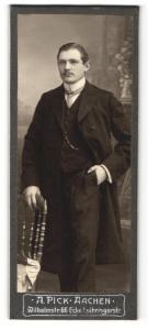 Fotografie A. Pick, Aachen, Portrait elegant gekleideter Herr mit Schnurrbart an Stuhl gelehnt