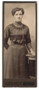 Fotografie W. Paulsen, Hamburg, Portrait hübsch gekleidete Dame mit Buch an Tisch gelehnt