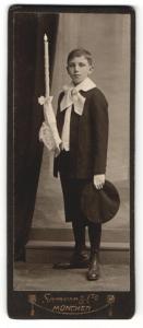 Fotografie Samson & Co. München, Junge mit Schleife im Anzug mit dekorierter Kerze