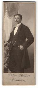Fotografie Atelier Makart, Züllichau, Portrait elegant gekleideter Herr mit Schnurrbart an Stuhl gelehnt