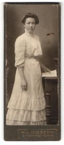 Fotografie J. Nissen, Gandersheim a / H., Portrait hübsch gekleidete Dame mit Zeitung an Tisch gelehnt