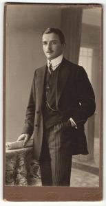 Fotografie J. Fuchs, Berlin, Portrait elegant gekleideter Herr mit Zeitung an Tisch gelehnt