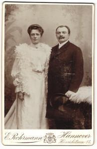 Fotografie E. Bohrmann, Hannover, Portrait bürgerliches Paar in eleganter Kleidung mit Hut