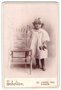Fotografie Scholten, St. Louis, Mo., Portrait hübsch gekleidetes Mädchen mit Feder an Stuhl gelehnt