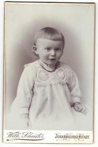 Fotografie Wilh. Schuster, Johanngeorgenstadt, Portrait hübsch gekleidetes Mädchen mit Ponyfrisur