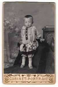Fotografie Cabinet-Portrait, unbekannter Ort, Portrait hübsch gekleidetes Kind mit Tasche auf Sessel stehend
