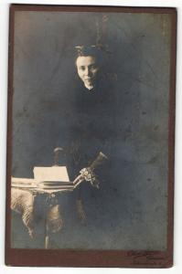 Fotografie T. Kuno Borst, Giessen, Portrait elegant gekleidete Dame mit Buch an Tisch gelehnt