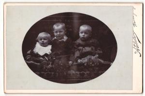 Fotografie unbekannter Fotograf und Ort, Portrait drei Kleinkinder auf Sitzmöbel