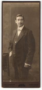 Fotografie Wilh. Husenbeth, Frankfurt / Main, Portrait dunkelhaariger charmant blickender Herr mit interessanter Fliege