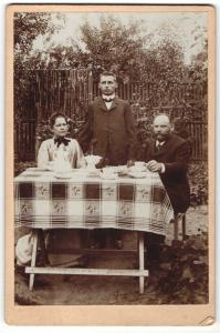 Fotografie unbekannter Fotograf und Ort, Portrait bürgerlich gekleidete Familie am Gartentisch sitzend
