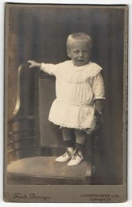 Fotografie Friedr. Deininger, Ludwigshafen a. Rh., Portrait hübsch gekleidetes Mädchen auf Stuhl stehend