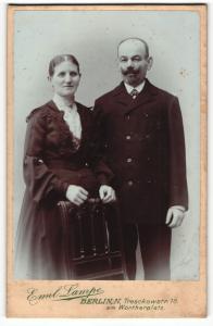 Fotografie Emil Lampe, Berlin-N, Portrait bürgerliches Paar in eleganter Kleidung an Stuhl gelehnt