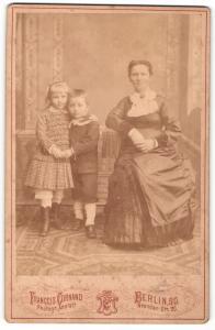Fotografie Francois Cornand, Berlin-SO, Portrait sitzende Mutter und zwei Kinder in festlicher Kleidung