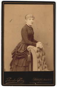 Fotografie Theodor Penz, Berlin-C, Portrait elegant gekleidete Dame mit Halskette an Sessel gelehnt