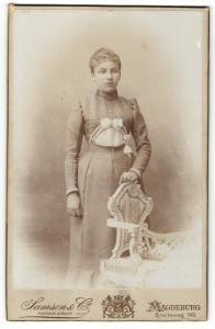Fotografie Samson & Co., Magdeburg, Portrait modisch gekleidete Dame mit Halskette an Bank gelehnt
