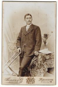 Fotografie Samson & Co., Magdeburg, Portrait bürgerlich gekleideter Herr mit Stuhl an Tisch gelehnt