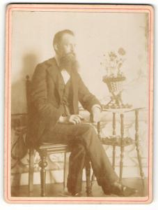 Fotografie unbekannter Fotograf und Ort, Portrait elegant gekleideter Herr mit Vollbart am Tisch sitzend