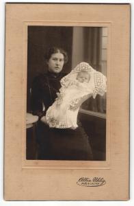 Fotografie Albin Uhlig, Aue i / S., Portrait stolze Mutter mit Baby im Arm am Tisch sitzend
