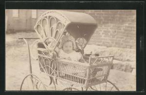 Foto-AK Baby sitzt im Korbkinderwagen