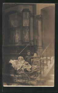 Foto-AK Zwei Kinder vor Hauseingang und Kleinkind in Kinderwagen