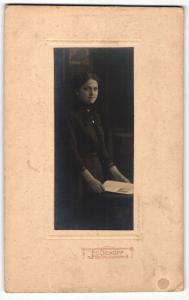 Fotografie Ed. Dickopf, Siegburg, Portrait elegant gekleidete Dame mit Zeitung an Tisch gelehnt